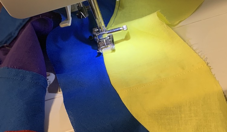 My sewing machine is shown while it top stitches the seam down between the blue and yellow swirl. Off to the left you can see the underside of the topstitched seam between the blue and purple swirls.