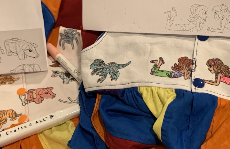 Part of both back bodices are visible in the image showing the KAMsnaps. The missing part of the image is drawn on with black ink. Above the outlines the coloring page rests.