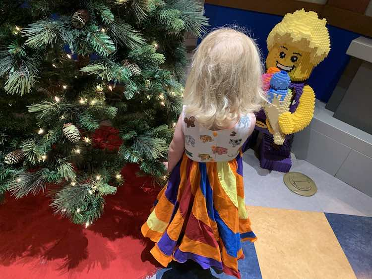 Zoey, wearing the dress, at LEGOLAND® standing in front of the Christmas tree looking at the LEGO® statue of the boy with his ice cream cone.