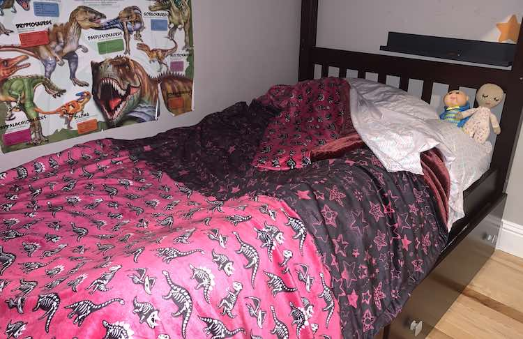 Image shows the lower bunk of our bunk bed with the bed made and the corner turned back invitingly. The top of the bed shows the newly made blanket.