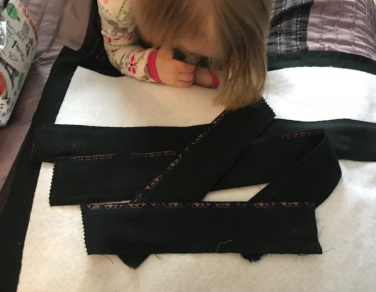 The four finished edges are laid overtop of the interfacing with the black fabric behind it. Ada's head is in view as she lays on her belly looking at the fabric with her magnifying glass.