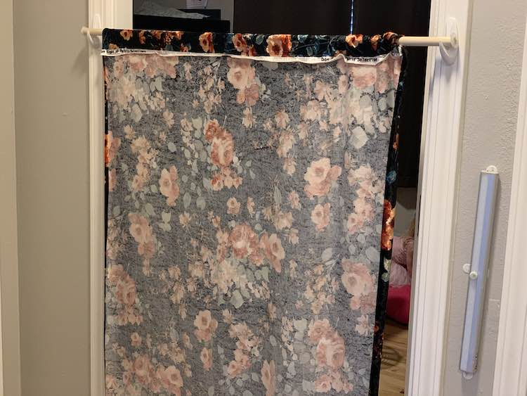 Closeup of the back of the curtain showing the folded over edge and seam. This time it's sitting in place in the bedroom doorway so the kids inside can see the flowers on the curtains.