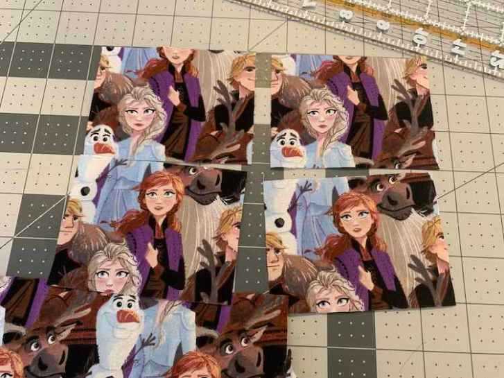 View of the four squares I cut out from the Frozen fabric I got from Walmart. The top two show Elsa's head with the surrounding characters cut off while the bottom two show, mainly, Anna.