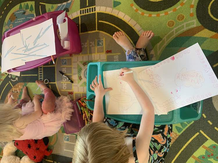 Image shows an overview of Ada and Zoey sitting on the car mat drawing on lap desks. Zoey is using decorative washi tape to attach to pieces of paper together artistically while Ada, to the right, follows the video to draw the pigeon from Mo Willems' book.