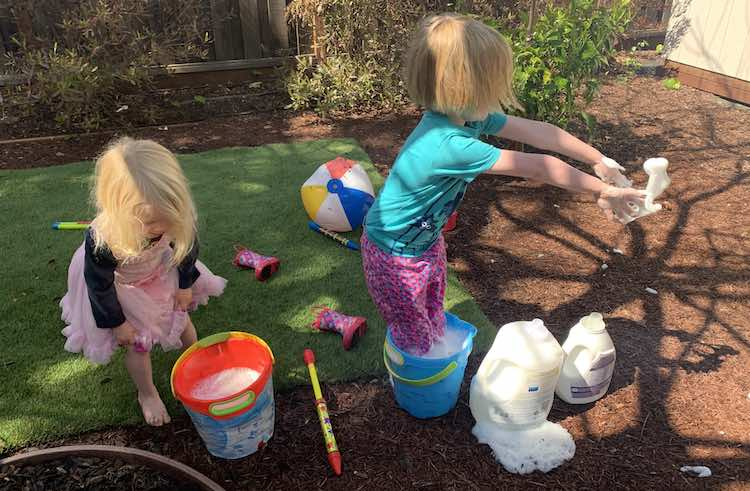 The photo was take outside. To the left Zoey is rolling up her pants about to get in the bucket of soapy water like her sister. To the right Ada is standing in her bucket of soapy water flinging some of the soap bubbles to the right.