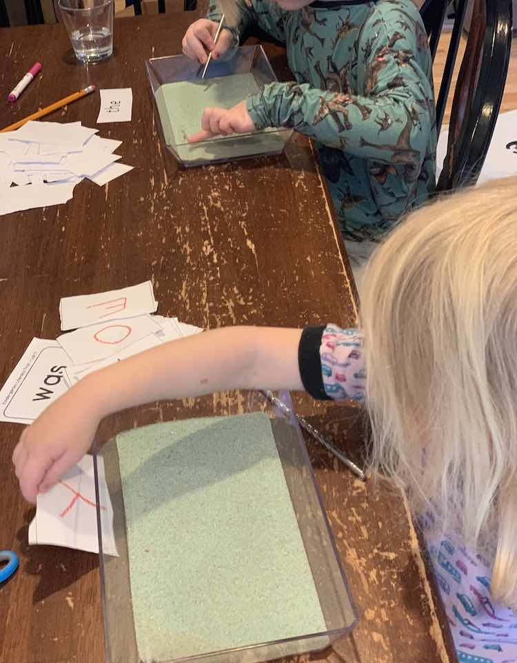 Bottom, forefront, of the image shows Zoey placing the letter 'y' behind the tray so she can sketch it out. In the background, further back, Ada has the 'the' played behind her tray and is drawing it out in her tray.