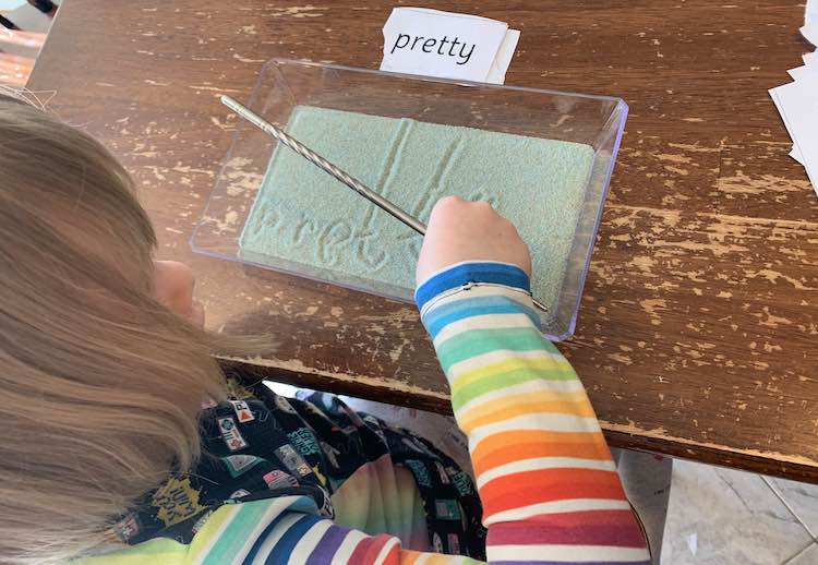 Ada, from above, writing out the word 'pretty'. Her hand obscures the y as she finishes off. The sight word is laid on the other side of the tray with the previously written sight words below it.