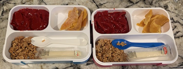 Closeup of both bento boxes showing the contents listed in the caption. Additionally, there's a plastic (Ikea) spoon laid out in the larger hole with the granola and slightly opened cheese string.