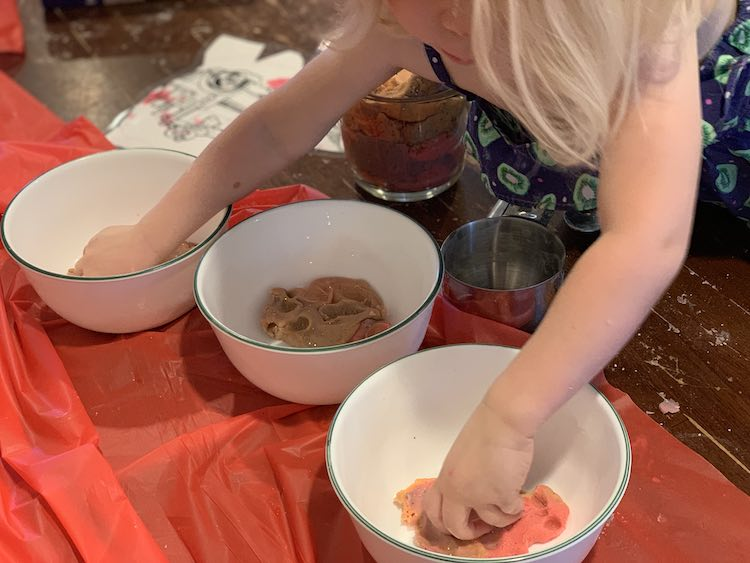 Image shows three white bowls with glittery playdough inside them. Zoey is leaned over the table with one hand in each of the outer two bowls. Under her sits a filled four cup jug with playdough and an empty metal measuring cup.
