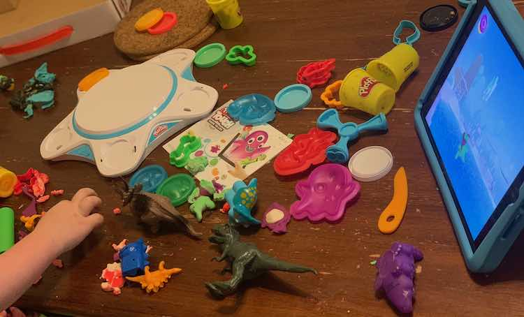 Image shows the kitchen table spread out with plastic dinosaurs and the Play-Doh kit. The iPad shows the playdough creation just as well as the old Play-Doh one.