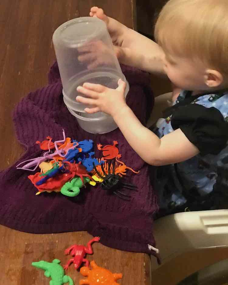 Zoey sits in a booster seat playing with two containers while her right foot rests beside it on the table. Under the containers is a kitchen towel with a pile of plastic animals. The end of the towel closest to use is extremely wet.