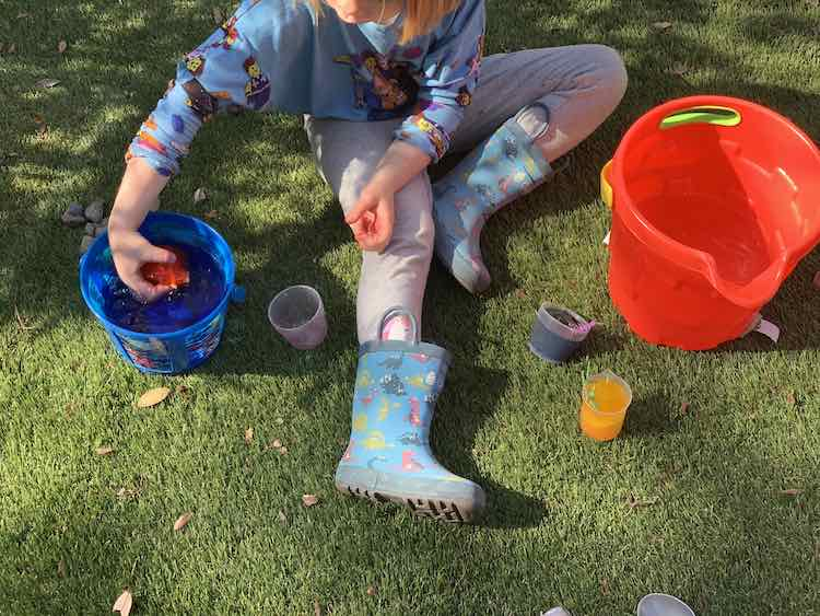 Overview of Ada sitting of fake grass with two buckets of water on either side. She has the filled blue and yellow cup near her leg and the emptied red cup on the other side. She is holding the red ice right above the water in the smaller blue bucket.