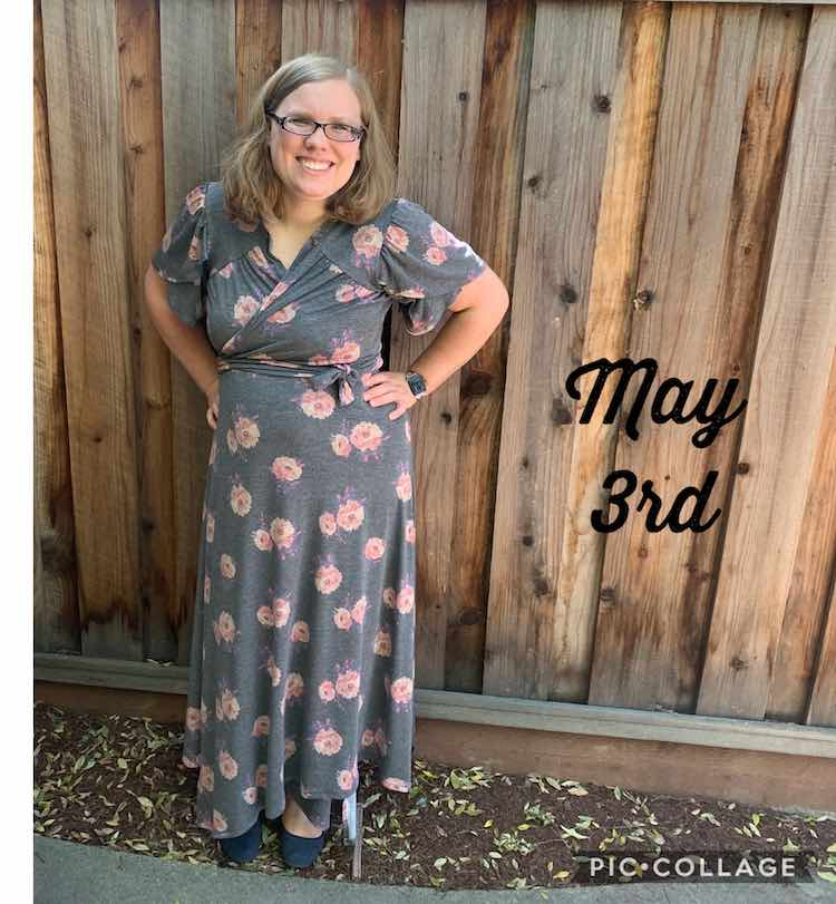 Me standing with my hand on my hips in front of a wooden fence. I'm wearing a grey wrap dress with pink flowers patterned on it. Beside me there's black font saying 'May 3rd'.
