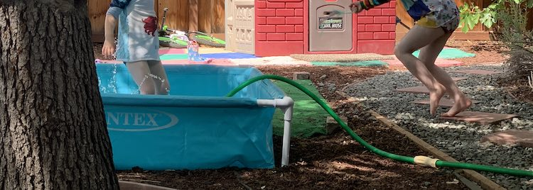 Short and wide image showing the Intex pool (left side of image with a sprinkler spraying up a bit and Zoey in it. To the right you can see the garden hose coming out over the side of the pool and Ada's feet as she rushes over.