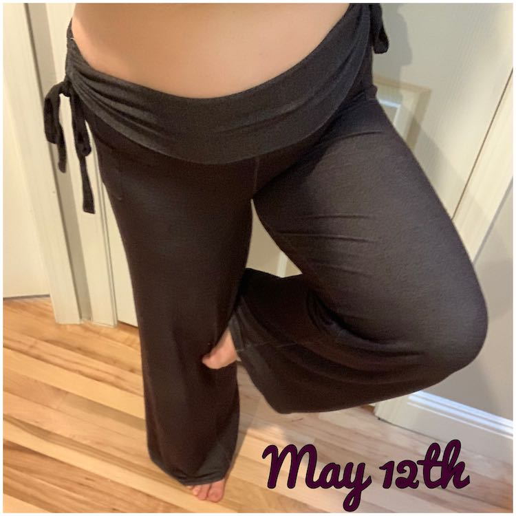 Closeup of my pants while I stand in flamingo pose (and lean over to selfie the picture). My shirt is pulled up so you can see the entire ruched waistband. The pants are long and loose and come just under my feet. At the bottom are the words 'May 12th'.