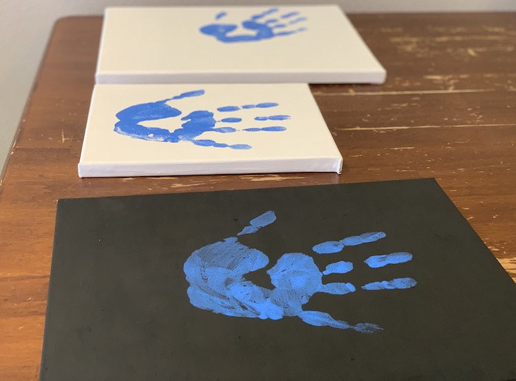 The three canvases laid out next to each other. In the image the canvases are turned sideways with the black one closest and the other two canvases beside it going further away. All three canvases have a blue handprint on it with the closest two centered in the middle and the furthest away one at an angle.