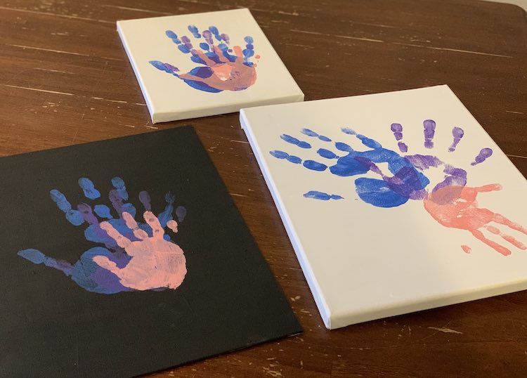 The three canvases are shown again with three handprints stamped on. The left (black) and right (white) canvases closer to the bottom of the photo are the larger ones while the smallest (white with stacked hands) is furthest away from the camera and is centered above the other two.