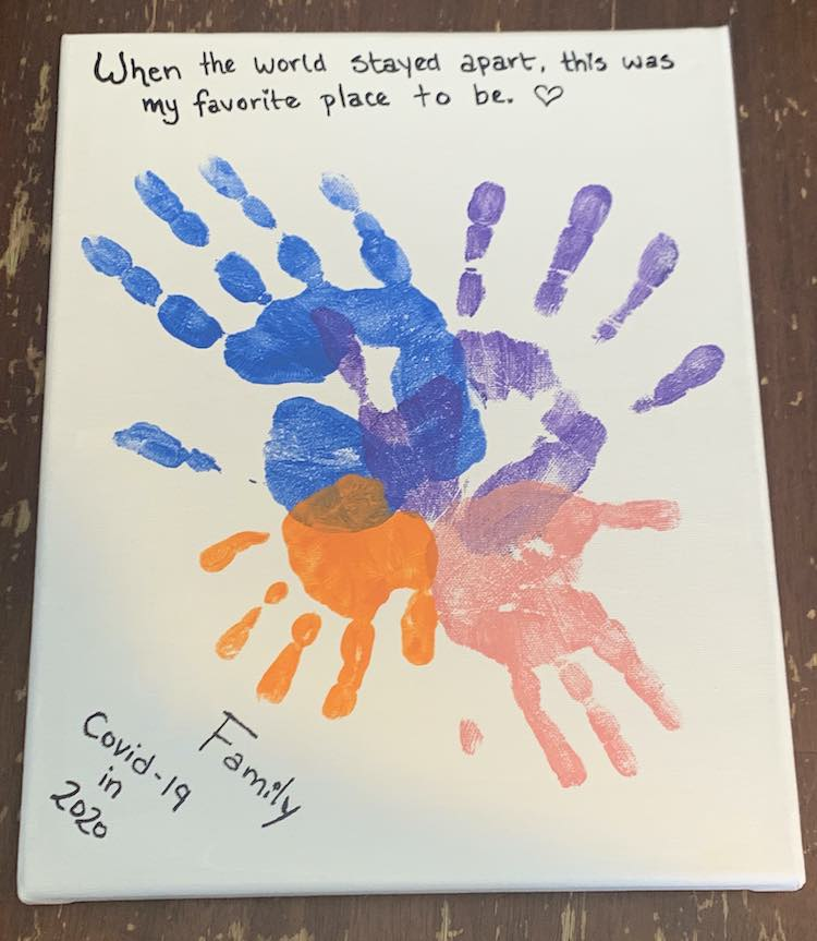 """This canvas was painted white and the four handprints were stamped with the palms slightly overlapping with the fingers spread outward into a circle. The largest blue handprint is on the upper left side and then the handprints decrease in size going around until it reaches the smallest orange handprint in the lower left side. The other two handprints are purple (upper right) and pink (lower right). Above the handprints are the words """"When the world stayed apart, this was my favorite place to be. <3"""". Below the hands several lines of text angled in the left corner reads """"Family/Covid-19/in/2020""""."""