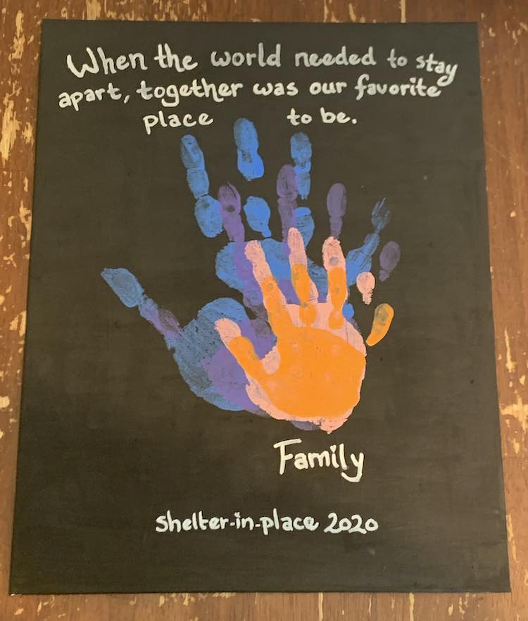 "The black canvas with the centered stacked hands reads ""When the world needed to stay apart, together was our favorite place to be."" above the hands while below it reads, over two lines, ""Last Name Family"" followed by ""shelter-in-place 2020""."