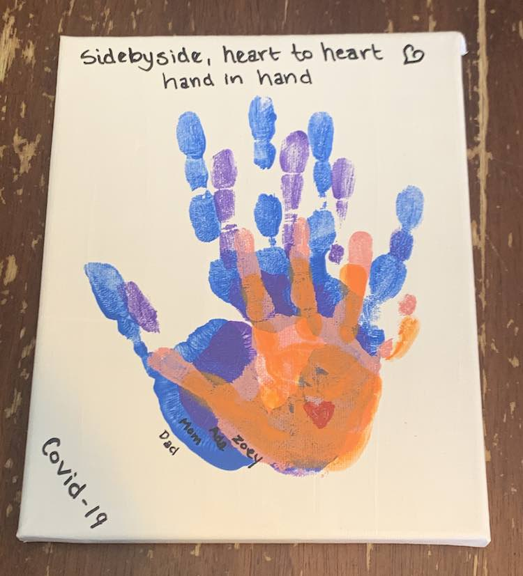 The small white canvas has all four hands stacked in the center with the lower right side of the palm lining up so the fingers, mostly, stand out. From largest to smallest it goes blue, purple, pink, and orange with a small red heart in the center of the orange palm. The names are written outside each handprint on the lower left side in black with an oil-based paint pen like I used with the other letters.