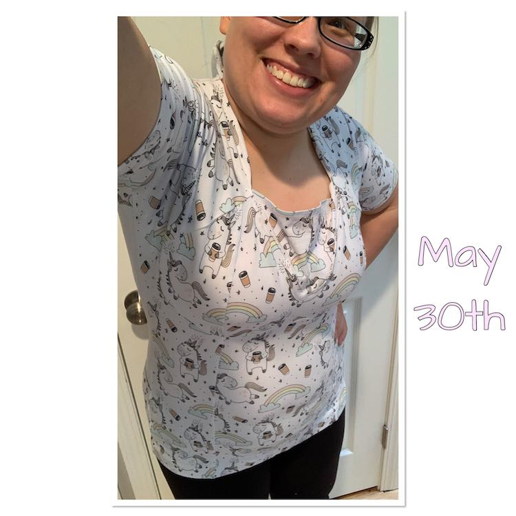 Selfie view showing a single eye down to the bottom of my shirt. The shirt is white with many rainbows, coffee cups, small hearts, and unicorns on it. If you look closely you can see the seam lines vertically over my stomach and showing the bra cups have been sewn together.