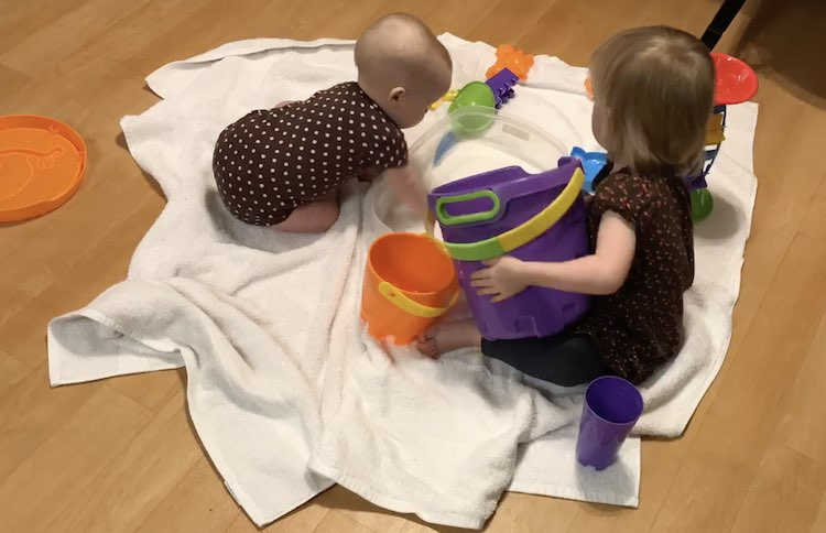 Zoey's hand reaches into the water as Ada (toddler) lifts the large bucket enough to pour more water into the plastic container.