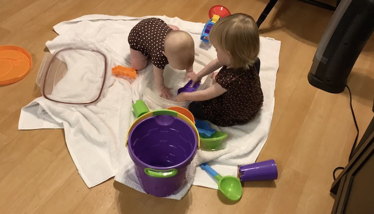 On the white towels on the ground are a clear bin with a baby playing while the toddler attempts to fill up her purple sand toy. Scattered around them are various other toys.