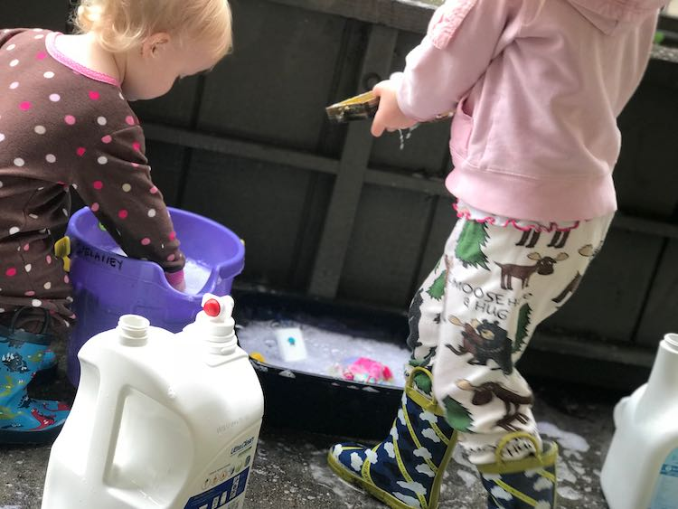 To the left Zoey leans over reaching into a purple sand pail filled with soapy water. To the right Ada walks towards Zoey carrying an item to the bin of soapy water. An emptied