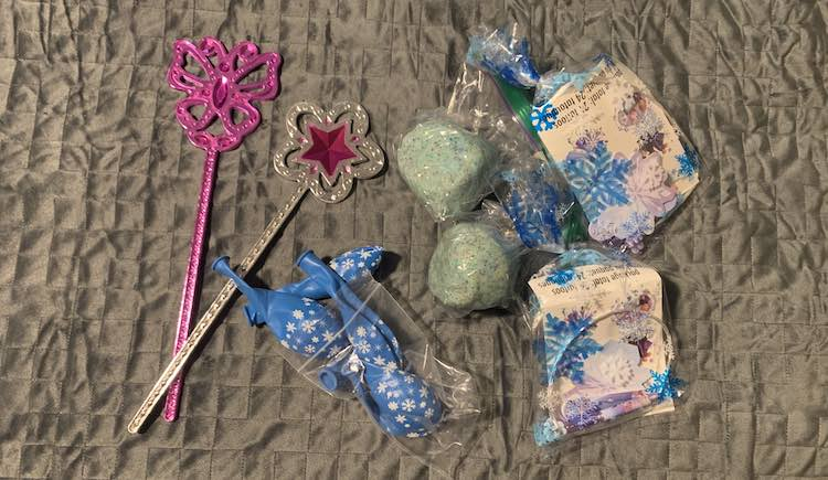 Top down view of two of the Melissa and Doug wands, a bag of blue snowflake latex balloons, two balls of gliittery blue playdough, and two clear cellophane bags with blue snowflake on it and Frozen items inside it.