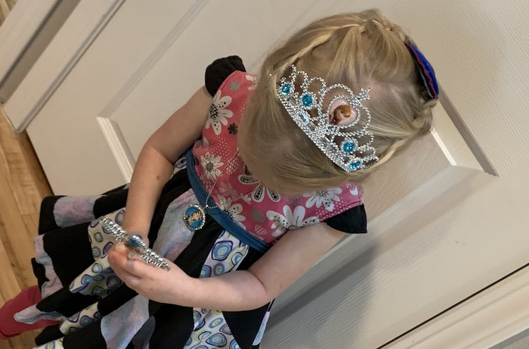 Front view of Zoey looking down to show the crown and top of her head. In her hands is the wand, hard to see, and around her neck is the new Anna necklace.
