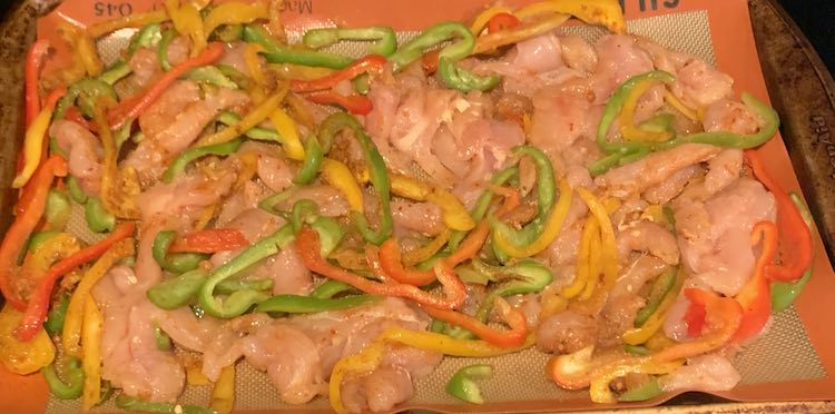 Closeup of the sheet pan showing raw pink chicken, sliced red peppers, sliced green peppers, and sliced onion.