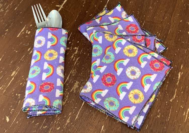 The photo shows a fork and spoon wrapped up in a napkin, on it's side, on the left of the photo. The right side of the photo shows the other four napkins folded in half and slightly overlapped making a slight arch going up the photo.