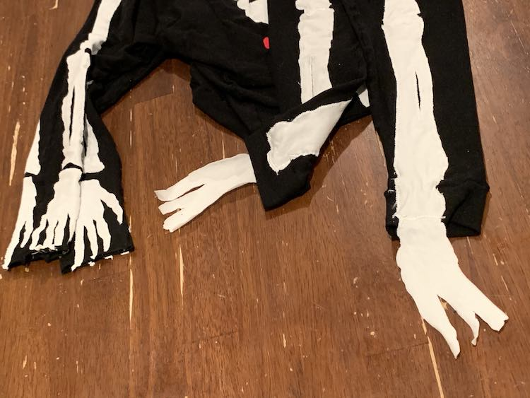 Image shows a closeup of the skeleton's hands and feet. The two sleeves are draped down from the top of the image on the left while the two feet drape down on the right. The one pant leg is folded up so you can see the backside and how the foot is only sewn on the front side.