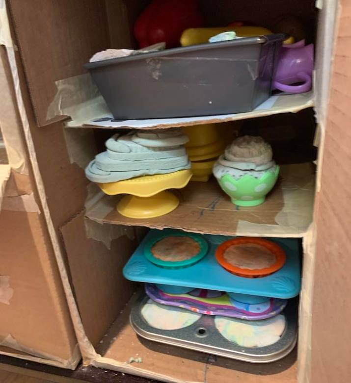 Image shows cardboard shelves surrounded by more cardboard in a table. The shelves are all filled with drying out playdough placed in either muffin tins, cake platter, loaf pan, or half a plastic Easter egg.