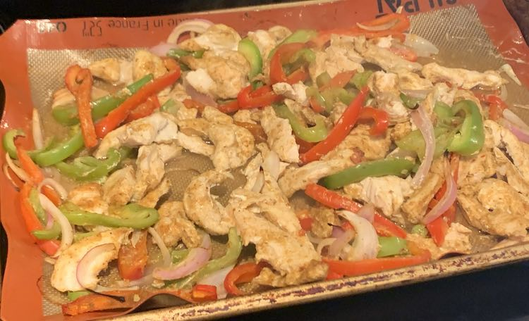 Closeup of the sheet pan showing baked white chicken, sliced red peppers, sliced green peppers, and sliced onion.