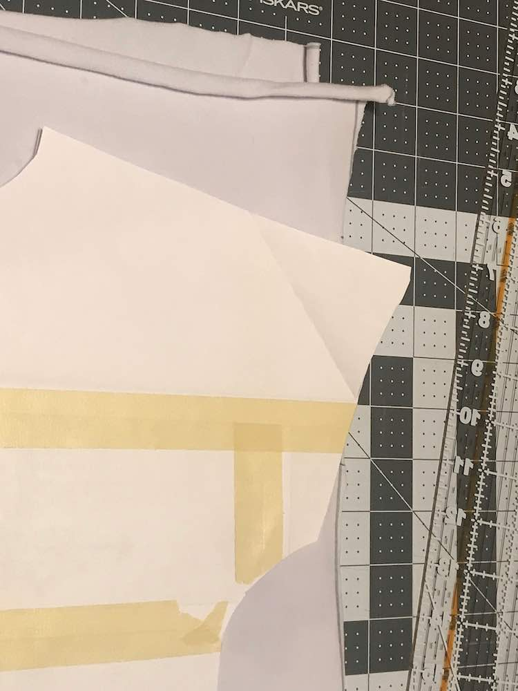 Overview showing the folded white panel with the paper pattern laying overtop of it. The top of the sleeve is jutting out over the fabric and doesn't fit. The background of the image shows a cutting mat and ruler.