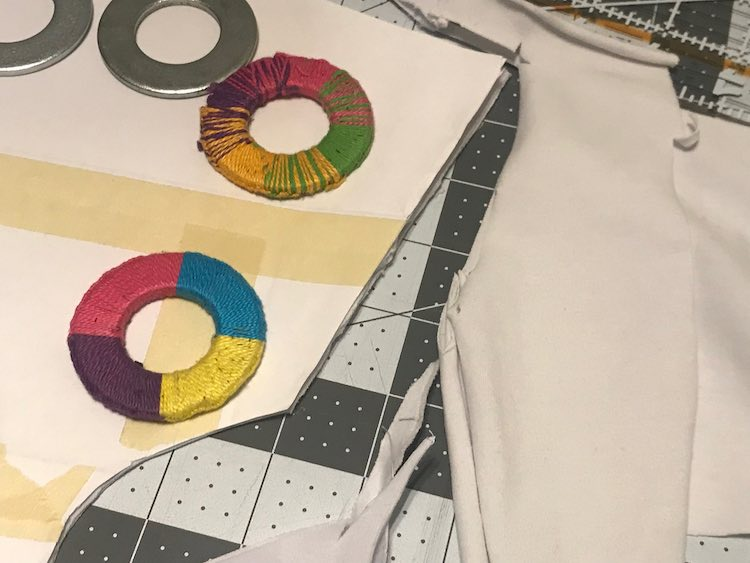 Image shows the same pattern piece over fabric with washers on it as before but this time the fabric around the pattern piece is cut and pulled away showing the cutting mat underneath it.