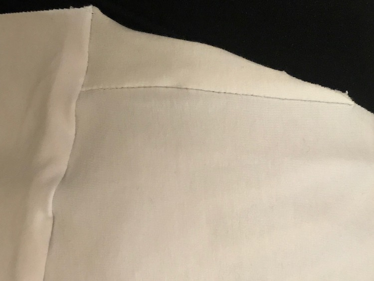 Closeup of the sewn on triangular section of the fabric with a black background. The trianlge is a right angle with the long end, at the bottom, attached to the front bodice to extend the panel. The left side is attached to the back bodice while the hypotenuse is along the sleeve part.