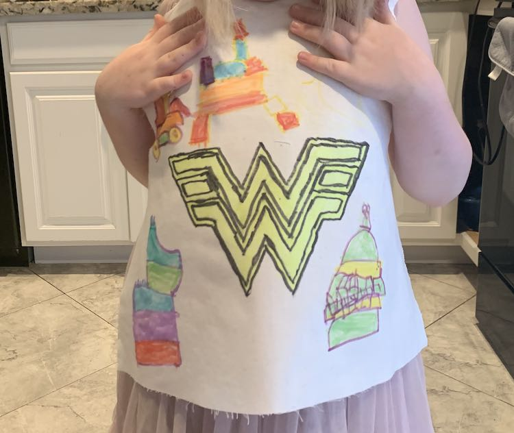 Image shows Ada standing in our kitchen holding up the white decorated front bodice piece so I could grab a photo of her with her creation.