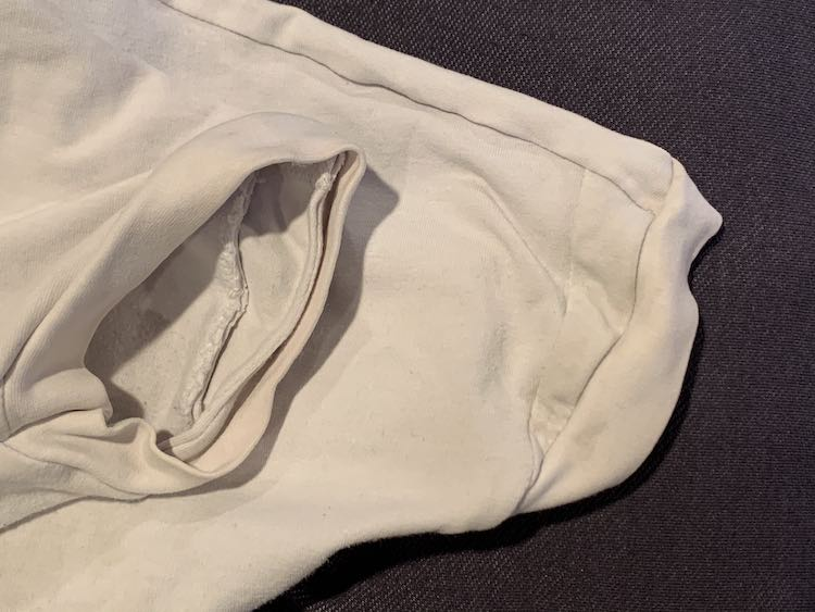 Image shows either sleeve, with the shirt folded in half, so you can see where the panel was extended. To the right you see the outside of the extension with a small triangle right before the sleeve's cuff. To the left you can see inside the sleeve showing the seam of that extension.