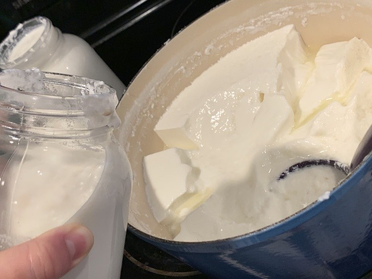 Shows my hand holding and tilting a 32 oz. canning jar over Dutch oven. There's a filled canning jar in the background. Inside the Dutch oven are clumps of yogurt within the whey liquid and you can barely see the purple plastic soup ladle sitting among the yogurt.