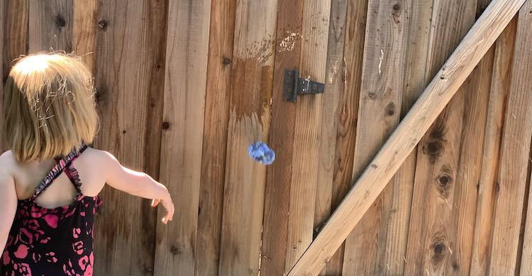 Ada's arm is now outstretched and angled downwards as she just finished throwing the ballon. The balloon is crumpled up a bit and is falling to the ground. Slightly above the balloon, on the fence, there's a wet splat mark where one of the sidewalk chalk targets were.