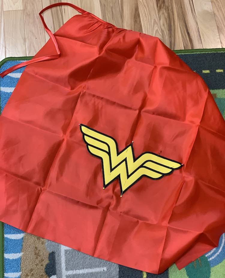 Closeup of the red cape with the black edged yellow Wonder Woman log pinned on. The yellow pins stand out at the top and bottom of the W but there are other smaller ones along the top of the logo too.