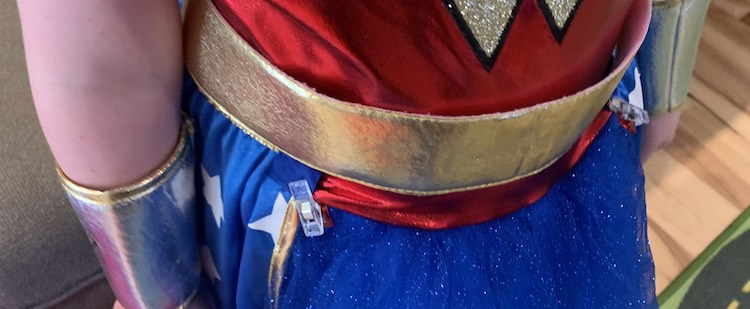 Closeup of the belt part of the dress. You can see a blue sewing clip holding the edge of the skirt overlay to the bottom of the red bodice fabric on either side.
