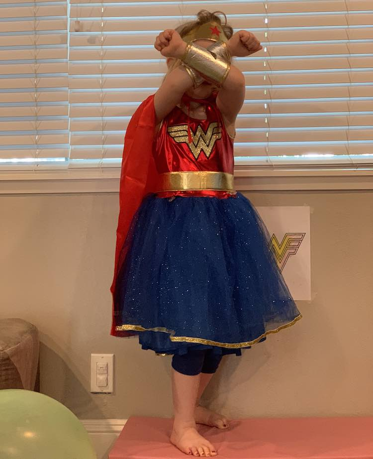 Front view of Ada in her costume including the skort and cape we added. Her arms are crossed in front of her face showing the arm guards and the tiara.