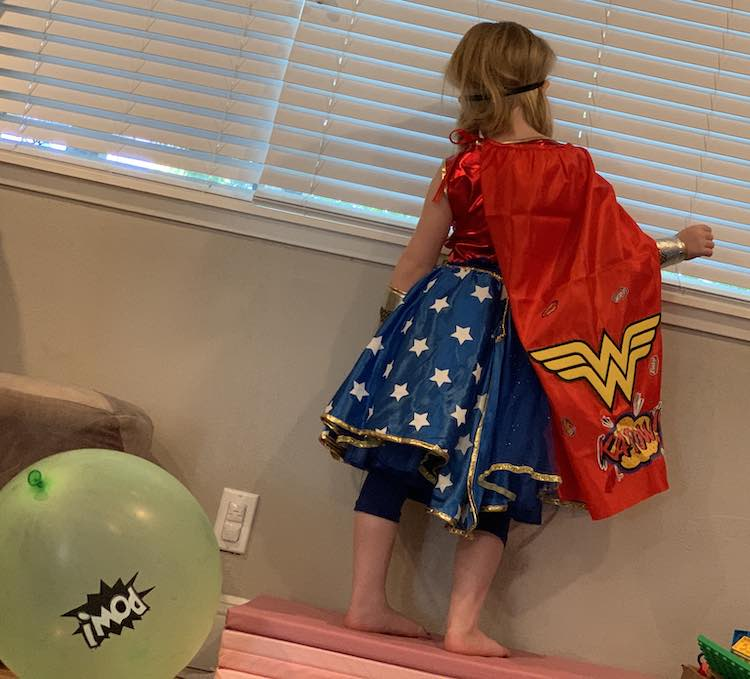 View from the back showing the skirt overlay starting to fall off, the decorated cape, and a POW balloon we added for super heroine training.