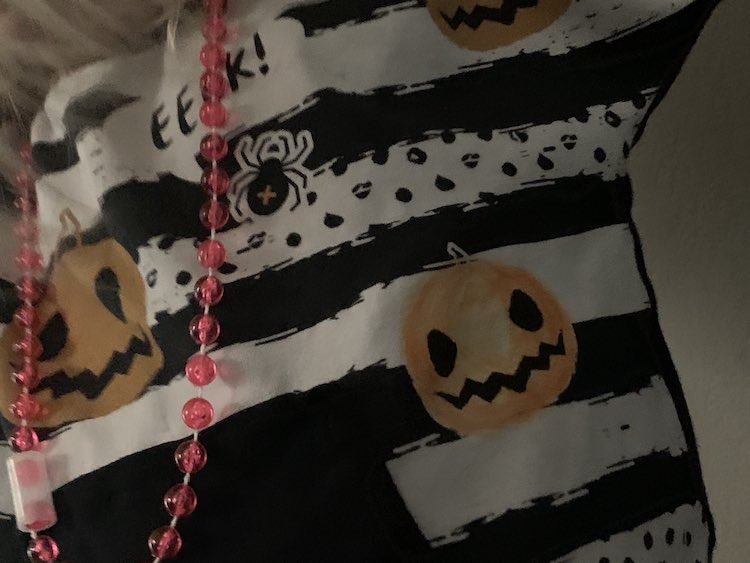 Image shows a closeup of a portion of a shirt mid torso. There's a pink necklace and black kangaroo pocket to the left. Above and beside the pocket sits a little jack-o-lantern that used to be white with black features and now is shaded with an orange fabric marker.