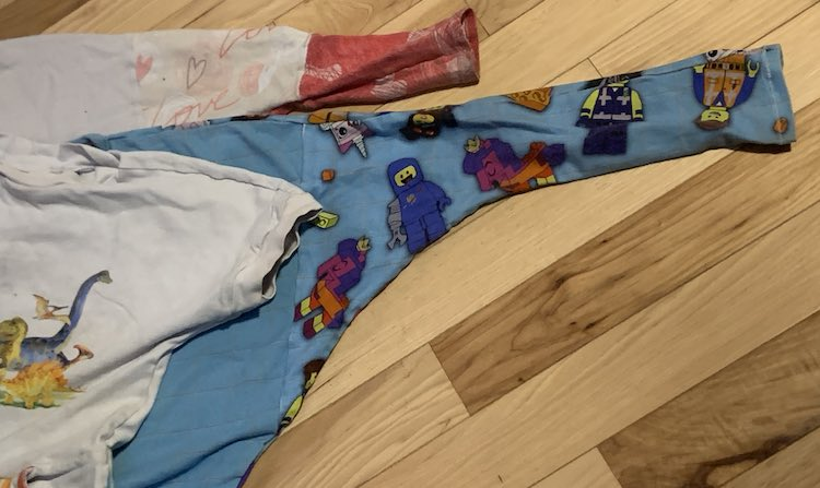 Three knit shirts laying on a wooden floor. You can only see a single sleeve of all three. The top is a white short sleeved dinosaur top with a small triangle right before the band at the sleeve. The next two shirts have a long sleeve. The middle blue one has a seam around the armpit while the bottom hearted one has three fabrics showing with the first seam halfway down the arm and another closer to the end where a wide band was added.