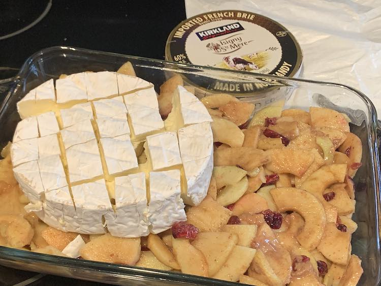 Image shows the glass casserole dish filled with a flat layer of apples, craisins, and sugar syrup. On the left sits a partially coming apart wheel of brie. Behind the casserole dish sits the flattened brie wrapper and the brie container from Costco.