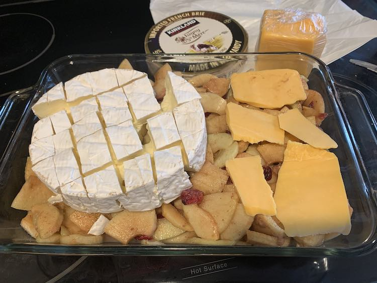 Image shows the casserole dish half filled with the apple pie filling. On the left sits the brie and on the right are five mismatched slices of orange cheddar cheese. Behind the casserole dish sits the brie wrapper and the wrapped leftover cheddar cheese.
